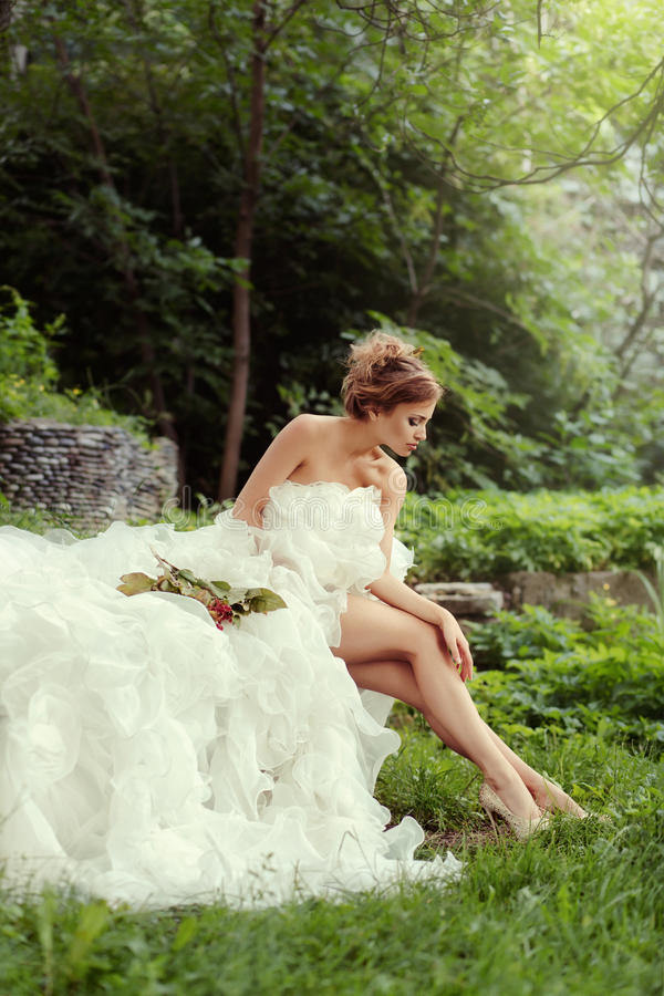 Beautiful woman bride looking at her long legs in nature in the forest. stock photography