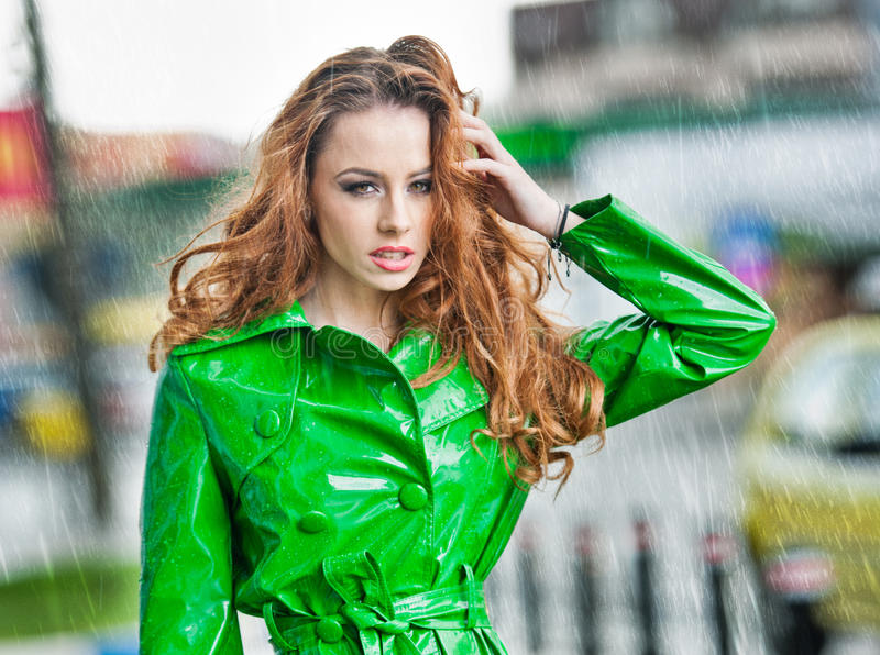 Beautiful woman in bright green coat posing in the rain royalty free stock photos