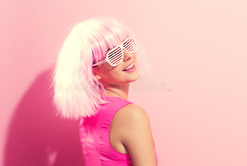 Beautiful woman in a bright pink wig. On a pink background stock images