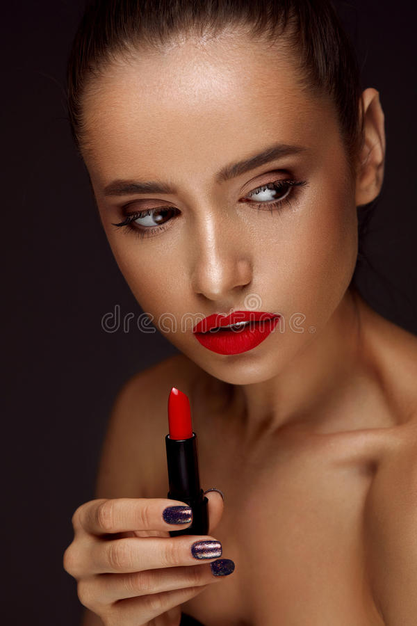 Beautiful Woman With Bright Red Lips And Lipstick In Hand royalty free stock image