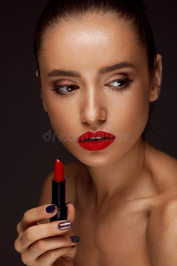 Beautiful Woman With Bright Red Lips And Lipstick In Hand. Beauty Makeup On Woman Face. Portrait Of Beautiful Girl With Red Lips, Long Eyelashes And Thick stock image