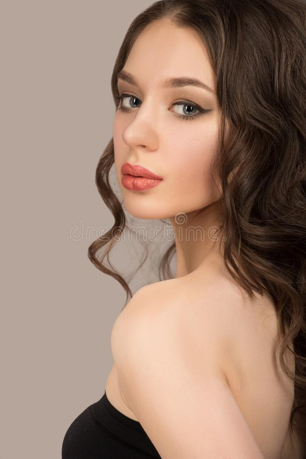 Beautiful woman with brown curly hair. Hairstyle. Gray background royalty free stock photo