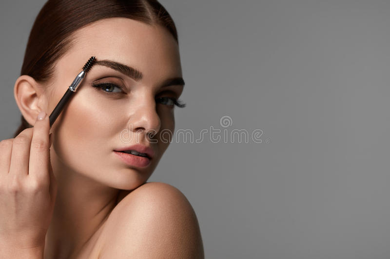 Beautiful Woman Brushing Eyebrows With Brow Tool royalty free stock photos