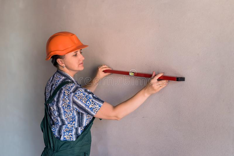 Beautiful woman builder working with water level stock photos
