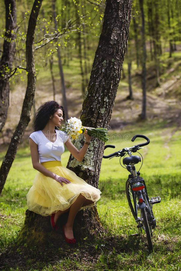 Beautiful woman with a bunch of snowdrops and a bicycle resting stock images