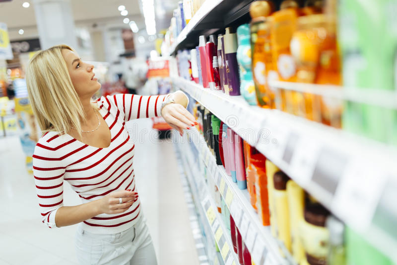 Beautiful woman buying body care products stock photos