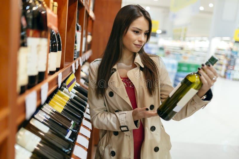 Beautiful woman buying wines stock image