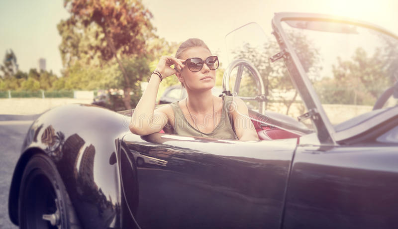Beautiful woman in cabriolet. Beautiful woman sitting in cabriolet, female enjoying trip on luxury modern car with open roof, fashionable lifestyle concept royalty free stock photos