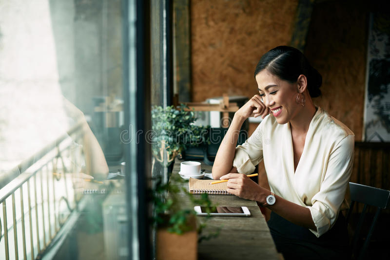 Beautiful woman in cafe. Cheerful business woman taking notes in notebook when having coffee in cafe stock photo