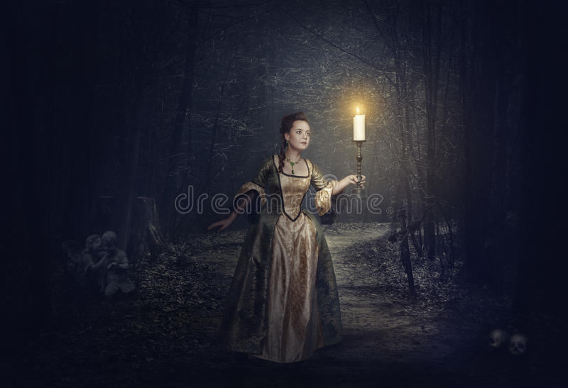 Beautiful woman with candle in medieval dress on the foggy road. Halloween landscape stock photo