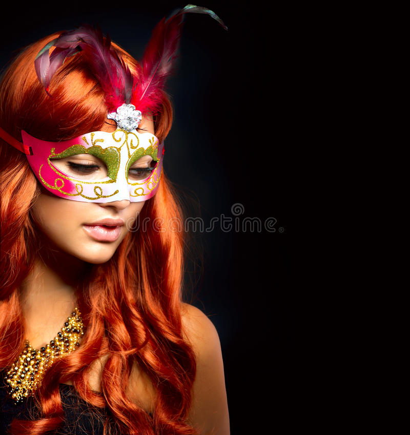 Beautiful Woman in a Carnival mask. Isolated on Black royalty free stock photos