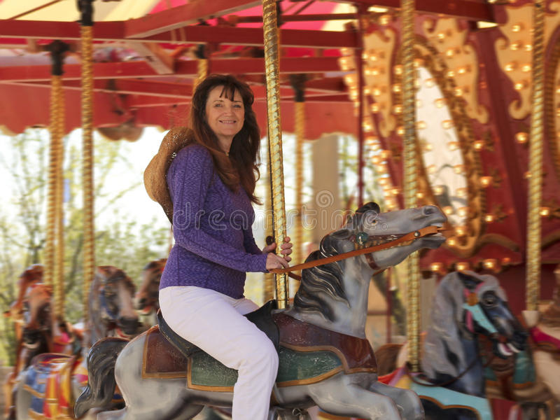 A Beautiful Woman on a Carousel. A Beautiful Woman Enjoys a Ride on a Merry-Go-Round royalty free stock photography