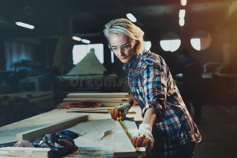 Beautiful woman carpenter designer works with ruler, make notches on the tree in workshop. Image of modern femininity. Concept o stock photos