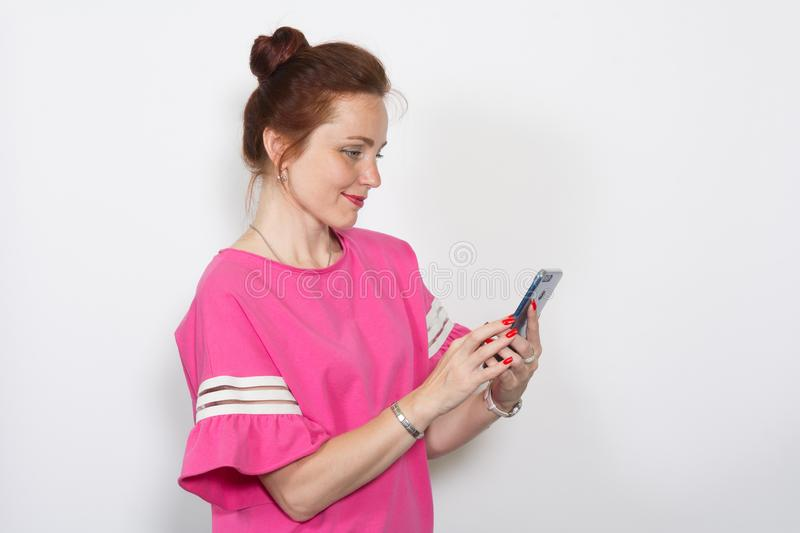 Beautiful woman in casual clothes holds in her hand a mobile phone stock images