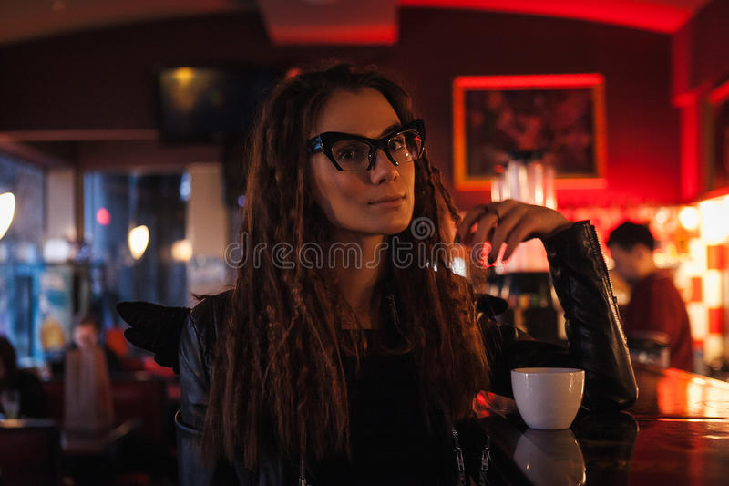 Beautiful woman in Cat`s eye glasses sitting near bar counter stock images
