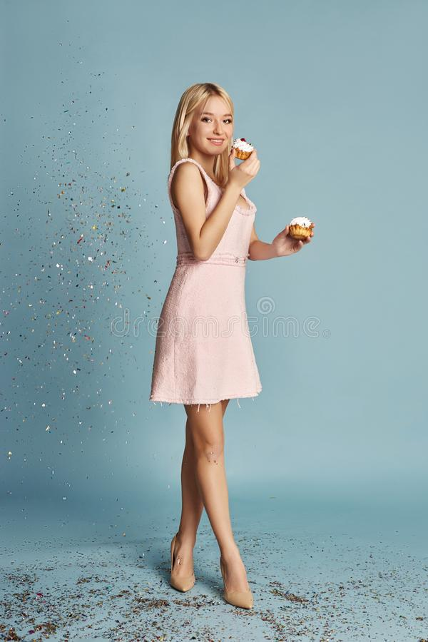 Beautiful Woman celebrating a birthday party having fun laughing and eating cakes under flying confetti. Girl posing and smiling. On blue background, cheerful royalty free stock images