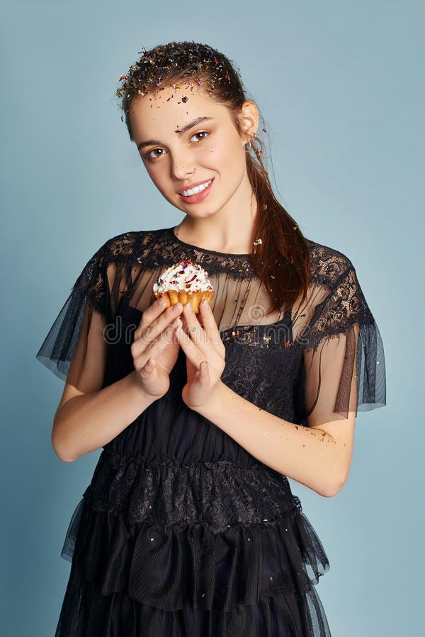 Beautiful Woman celebrating a birthday party having fun laughing and eating cakes under flying confetti. Girl posing and smiling royalty free stock photos