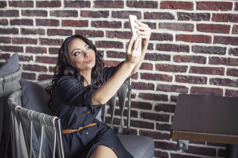 Beautiful woman in a chair in the restaurant is making selfie on royalty free stock photography