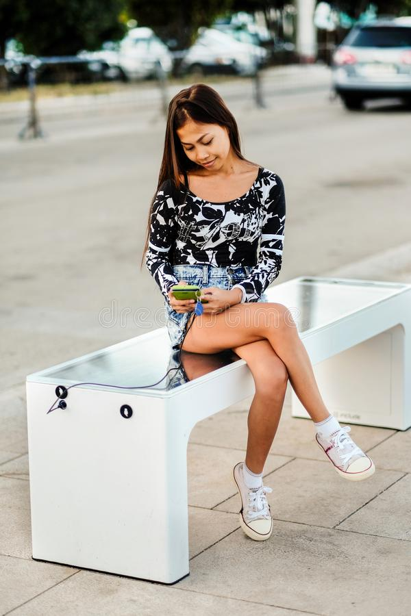 Beautiful woman charging her phone on free multipurpose solar panel charger incorporated in to sitting bench for citizens.Modern t royalty free stock photo