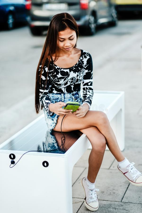 Beautiful woman charging her phone on free multipurpose solar panel charger incorporated in to sitting bench for citizens.Modern t stock photo