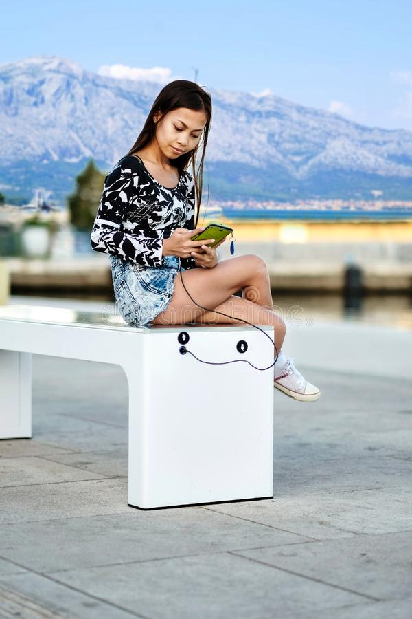 Beautiful woman charging her phone on free multipurpose solar panel charger incorporated in to sitting bench for citizens.Modern t. Echnology free energy for stock photo