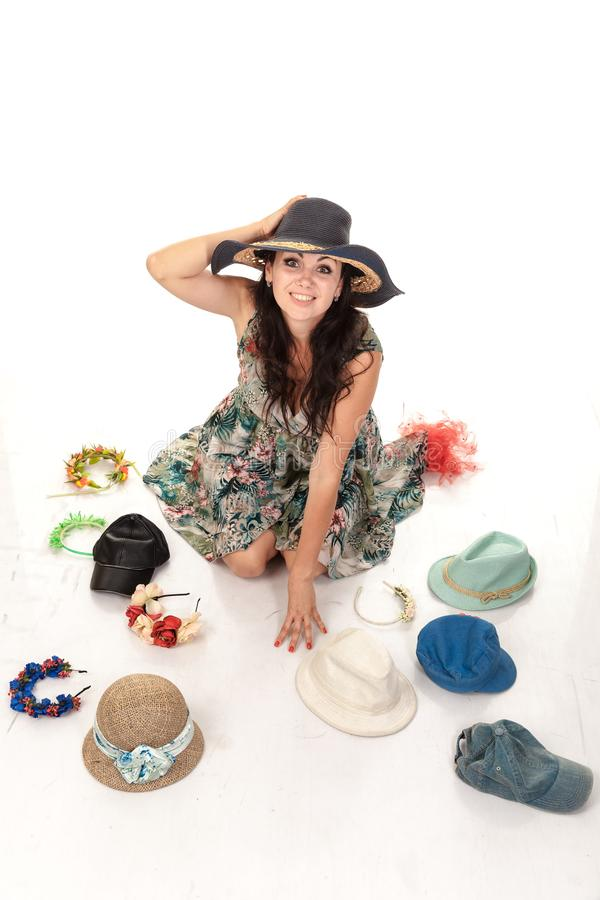 Beautiful woman chooses hats. Sits on the floor, trying on headgear. Many different hats, bonnet. Isolated photo on the white back stock photography
