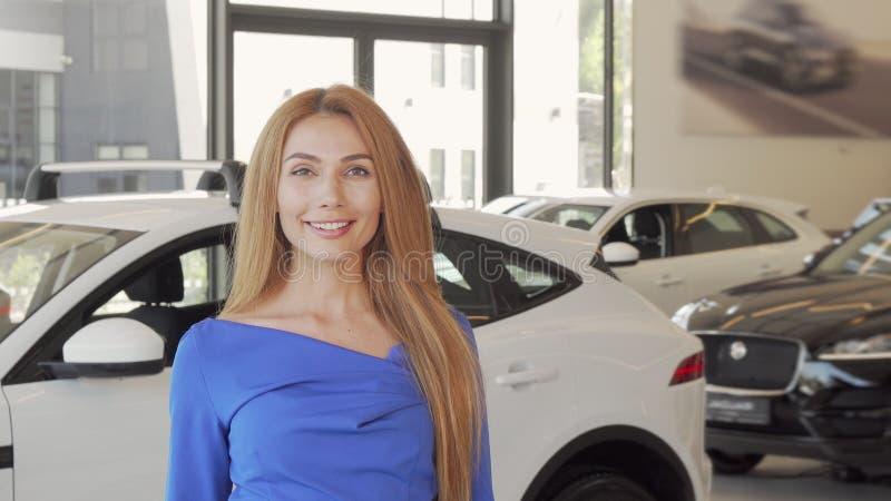 Beautiful woman choosing automobile to buy at dealership salon royalty free stock image