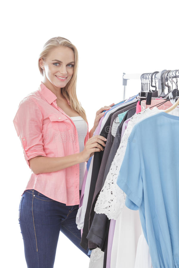 Beautiful woman choosing clothes at clothing store stock photography