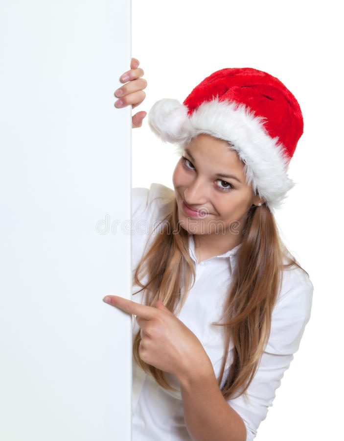 Beautiful woman with christmas hat pointing on a signboard. Cheering woman with long blond hair and a funny christmas hat pointing on a signboard stock photography