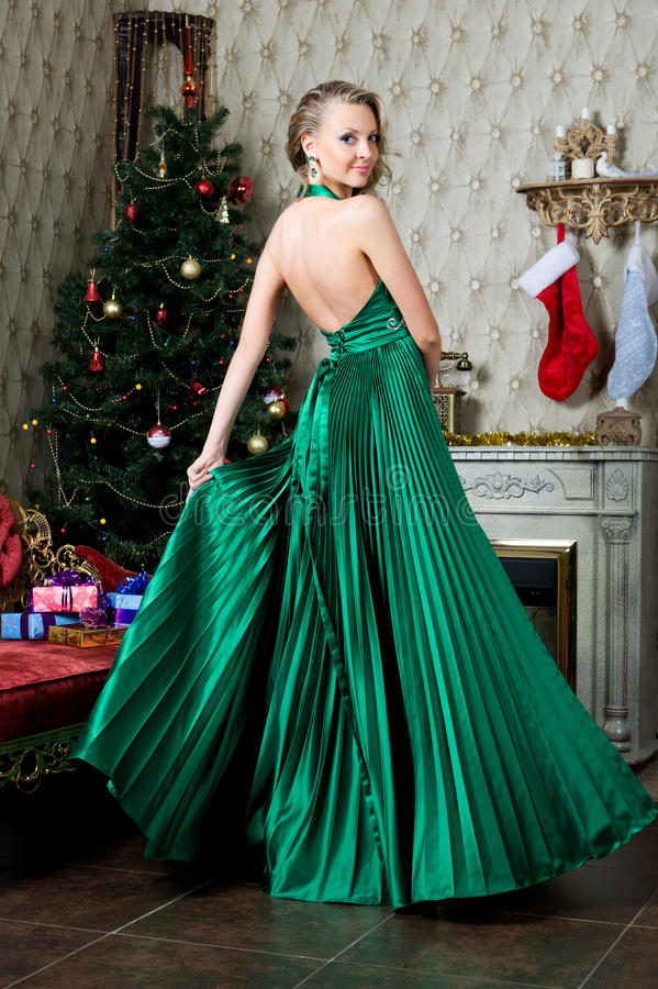Beautiful woman at the Christmas tree. Portrait of the Beautiful woman at the Christmas tree royalty free stock photo