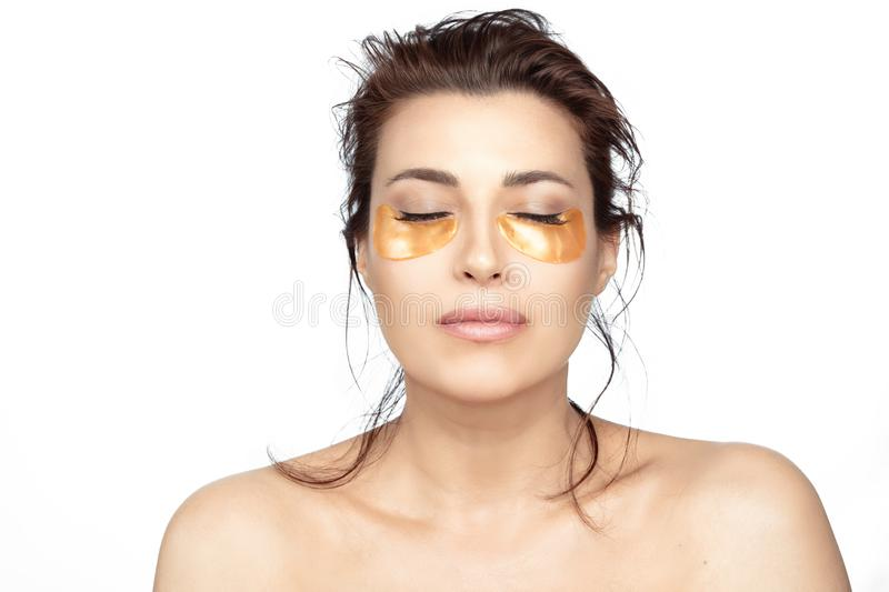 Beautiful woman with clean fresh skin using collagen eye pads under eyes stock images