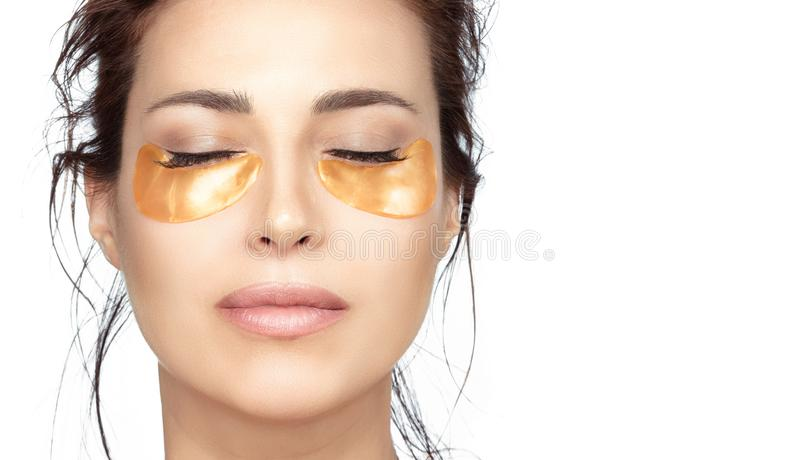 Beautiful woman with clean fresh skin using collagen eye pads under eyes royalty free stock photography