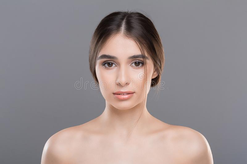 Beautiful woman with clean skin and natural makeup. On grey background stock image