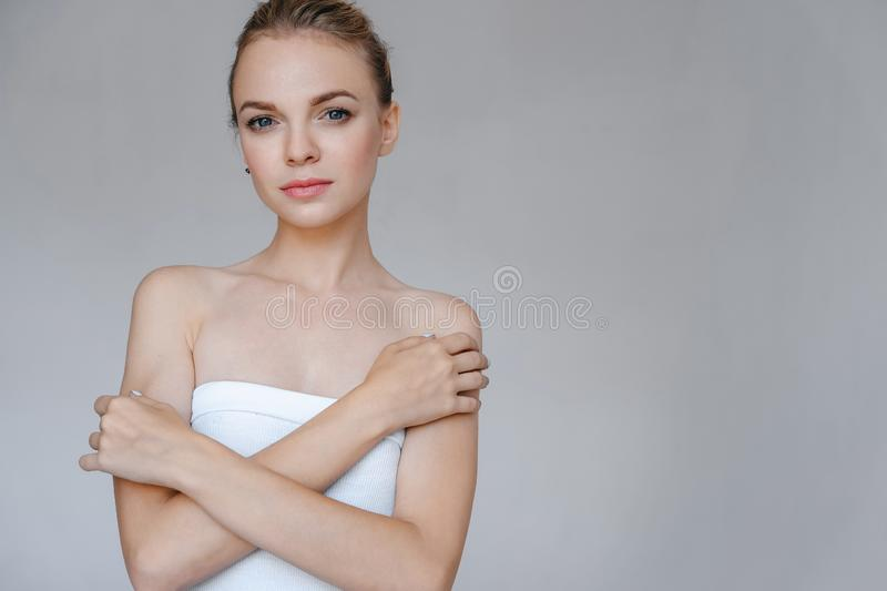 Beautiful woman with clean skin in white clothes hugged herself. Studio portrait stock photos