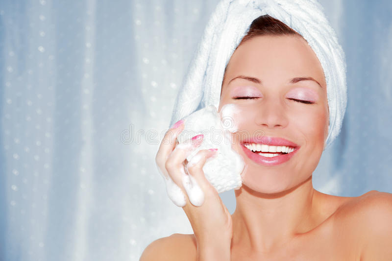 Beautiful woman cleaning face. Portrait of beautiful woman cleaning face. Beauty treatment stock photo