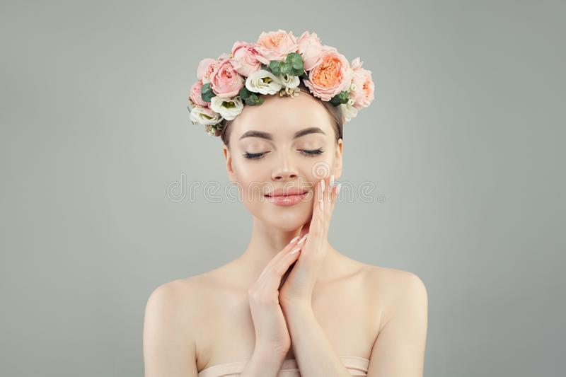 Beautiful woman with clear skin, flowers and manicure nails relaxing. Skin care, facial treatment and relaxation concept.  stock photo