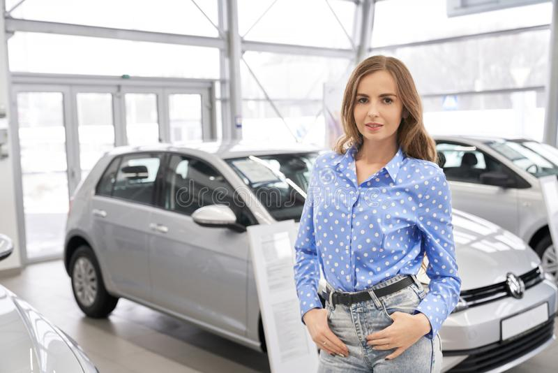 Beautiful woman, client of car dealership posing in showroom stock images