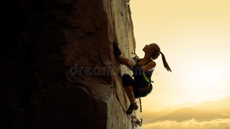 Beautiful Woman Climbing on the Rock at Foggy Sunset in the Mountains. Adventure and Extreme Sport Concept stock photos