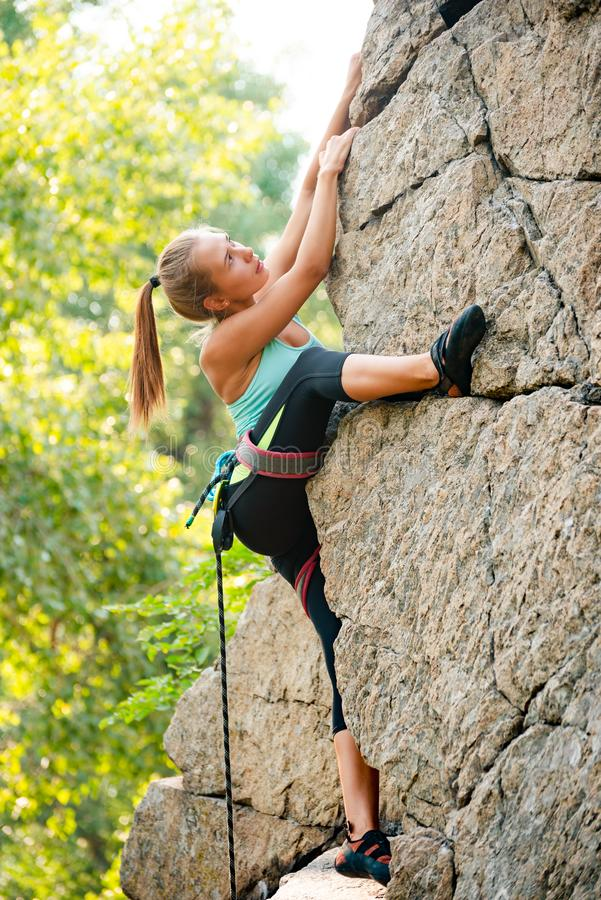 Beautiful Woman Climbing on the Rock in the Mountains. Adventure and Extreme Sport Concept royalty free stock photo