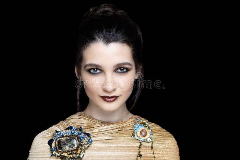 Massive art accessory, golden blouse. Beautiful woman close up portrait. Professional make up glossy eyeshadows, long lashes, new matte brown lipstick. Elegant stock photo