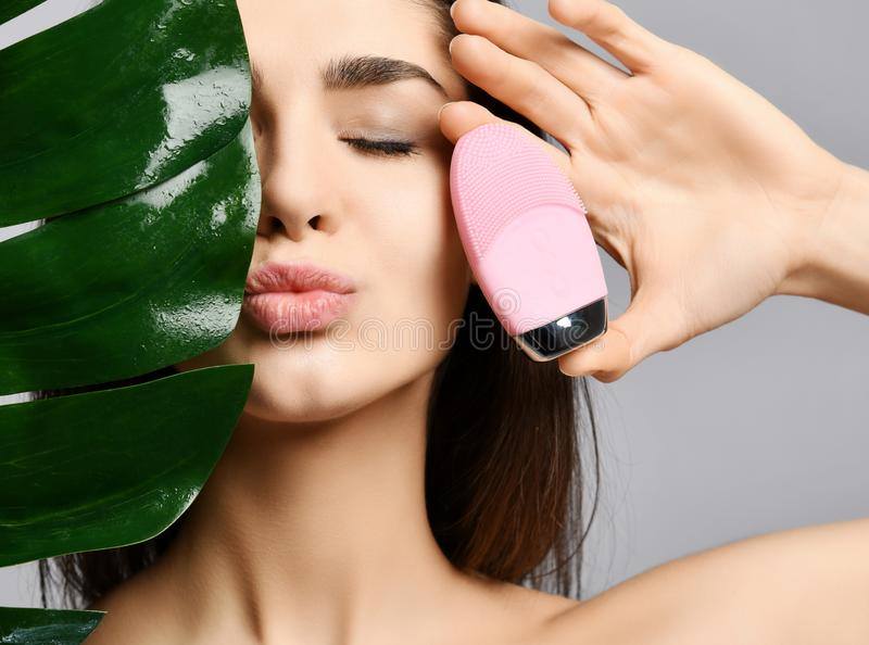 Pretty woman with closed eyes holds pink face exfoliator brush cleansing device for skin and large green leaf sends a kiss. Beautiful woman with closed eyes royalty free stock photo