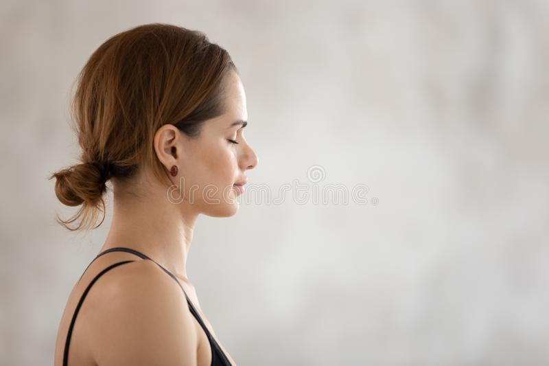 Beautiful woman with closed eyes practicing yoga, meditating, profile view. Profile view beautiful woman with closed eyes practicing yoga, meditating, attractive royalty free stock photo