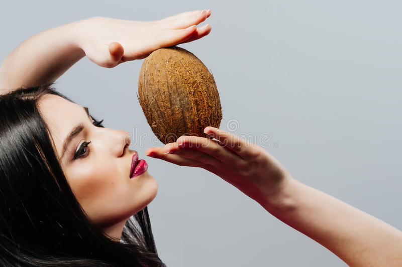 Beautiful woman with coconut in hands over white background, fashion portrait royalty free stock images