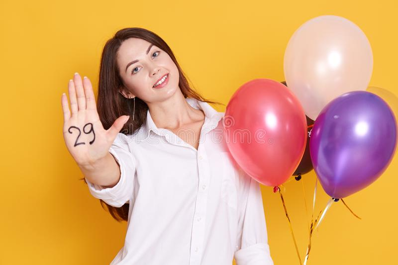 Beautiful woman with colored balloons posing in studio isolated over yellow background. Happy young female celebrates birthday royalty free stock photo
