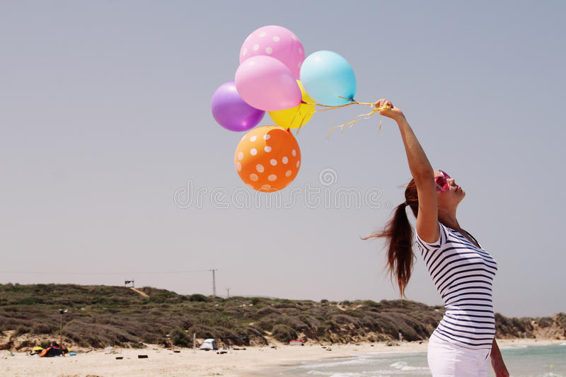 Beautiful woman with colorful balloons. On seaside stock photo