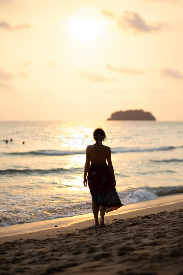 Beautiful woman in a colorful summer dress walking on the Thailand Ko Chang beach with beautiful white send during a. Sunset - Travel photo stock images