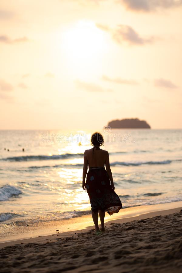 Beautiful woman in a colorful summer dress walking on the Thailand Ko Chang beach with beautiful white send during a. Sunset - Travel photo stock photos