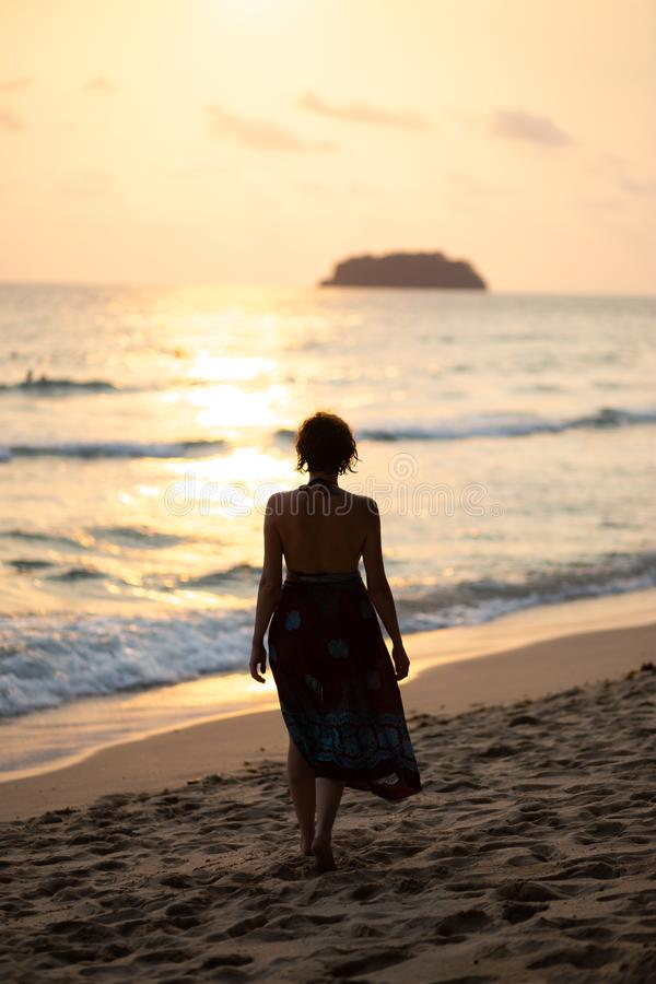 Beautiful woman in a colorful summer dress walking on the Thailand Ko Chang beach with beautiful white send during a. Sunset - Travel photo stock photography