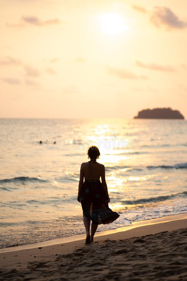 Beautiful woman in a colorful summer dress walking on the Thailand Ko Chang beach with beautiful white send during a. Sunset - Travel photo stock image