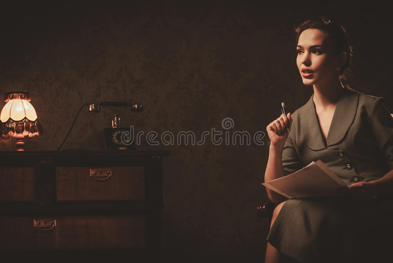 Beautiful woman composing letter in retro interior. Beautiful young woman in retro interior stock photography